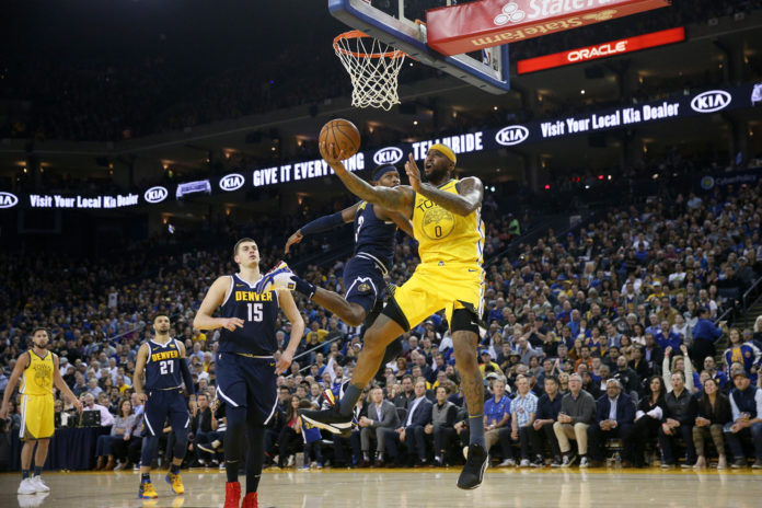 Golden State Warriors center DeMarcus Cousins (0) makes a layup next to Denver Nuggets forward Torrey Craig (3) in the second quarter at Oracle Arena.