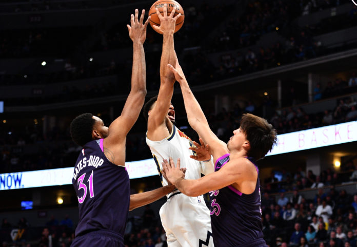 Minnesota Timberwolves forward Keita Bates-Diop (31) and forward Dario Saric (36) defend against Denver Nuggets guard Jamal Murray (27) in the first quarter at the Pepsi Center.