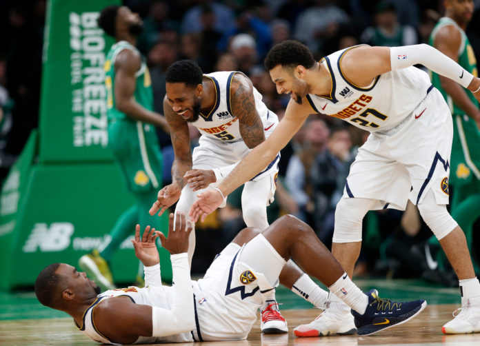 Denver Nuggets guard Will Barton (5) and guard Jamal Murray (27) celebrate with center Paul Millsap (4) during the second half against the Boston Celtics at TD Garden.