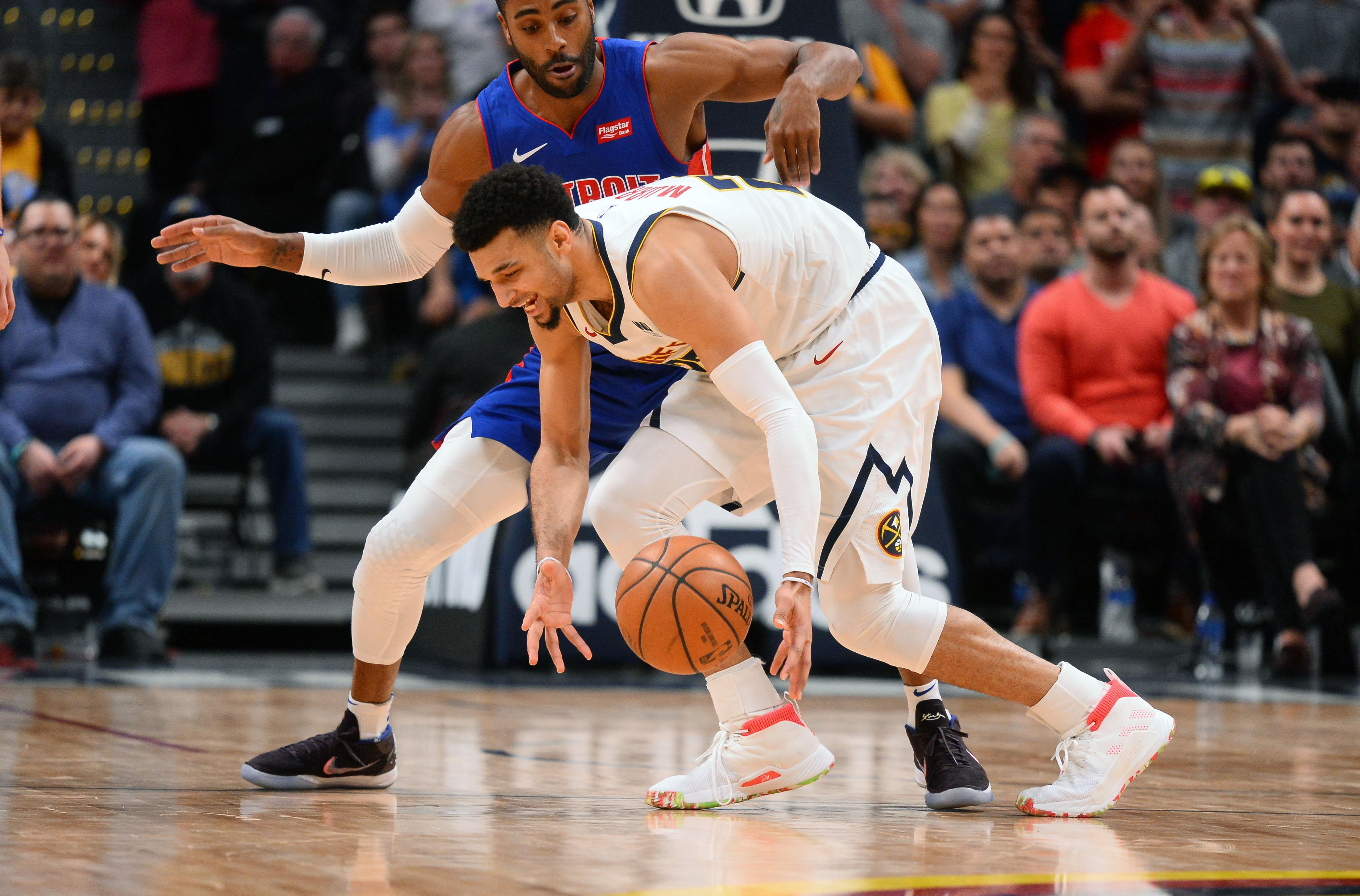 Detroit Pistons guard Wayne Ellington (top) pressures Denver Nuggets guard Jamal Murray (27) in the second half at the Pepsi Center.