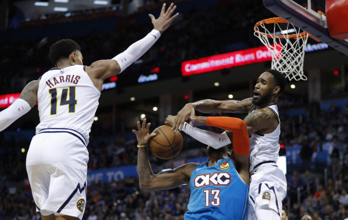 Oklahoma City, OK, USA; Oklahoma City Thunder forward Paul George (13) is fouled by Denver Nuggets guard Will Barton (5) as guard Gary Harris (14) defends during the second half at Chesapeake Energy Arena. Denver won 115-105.