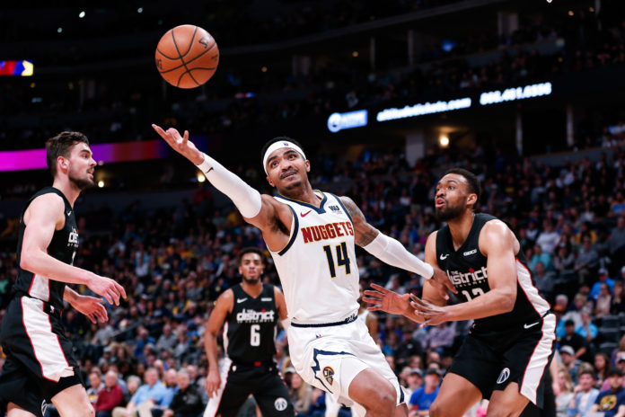 Denver Nuggets guard Gary Harris (14) grabs for a loose ball against Washington Wizards forward Jabari Parker (12) in the second quarter at the Pepsi Center.