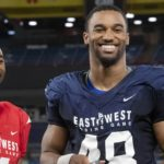 Justin Hollins (right) receives an award as the defensive MVP of the East-West Shrine Game.