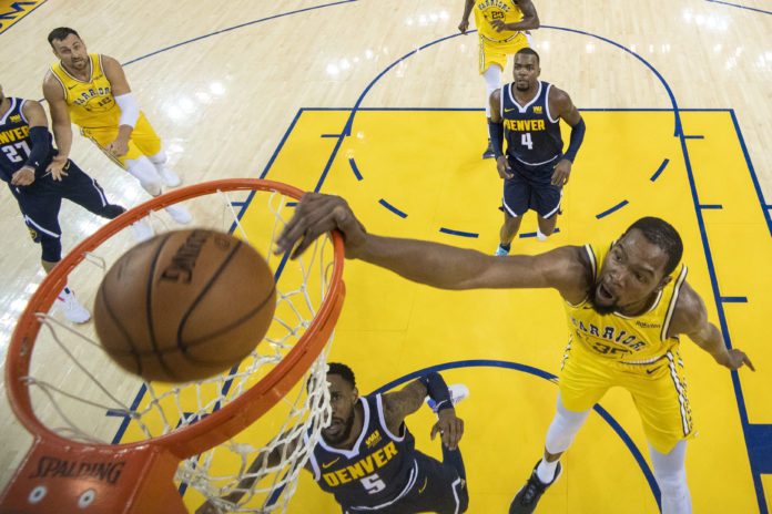 Golden State Warriors forward Kevin Durant (35) dunks the basketball against Denver Nuggets guard Will Barton (5) during the first half at Oracle Arena.