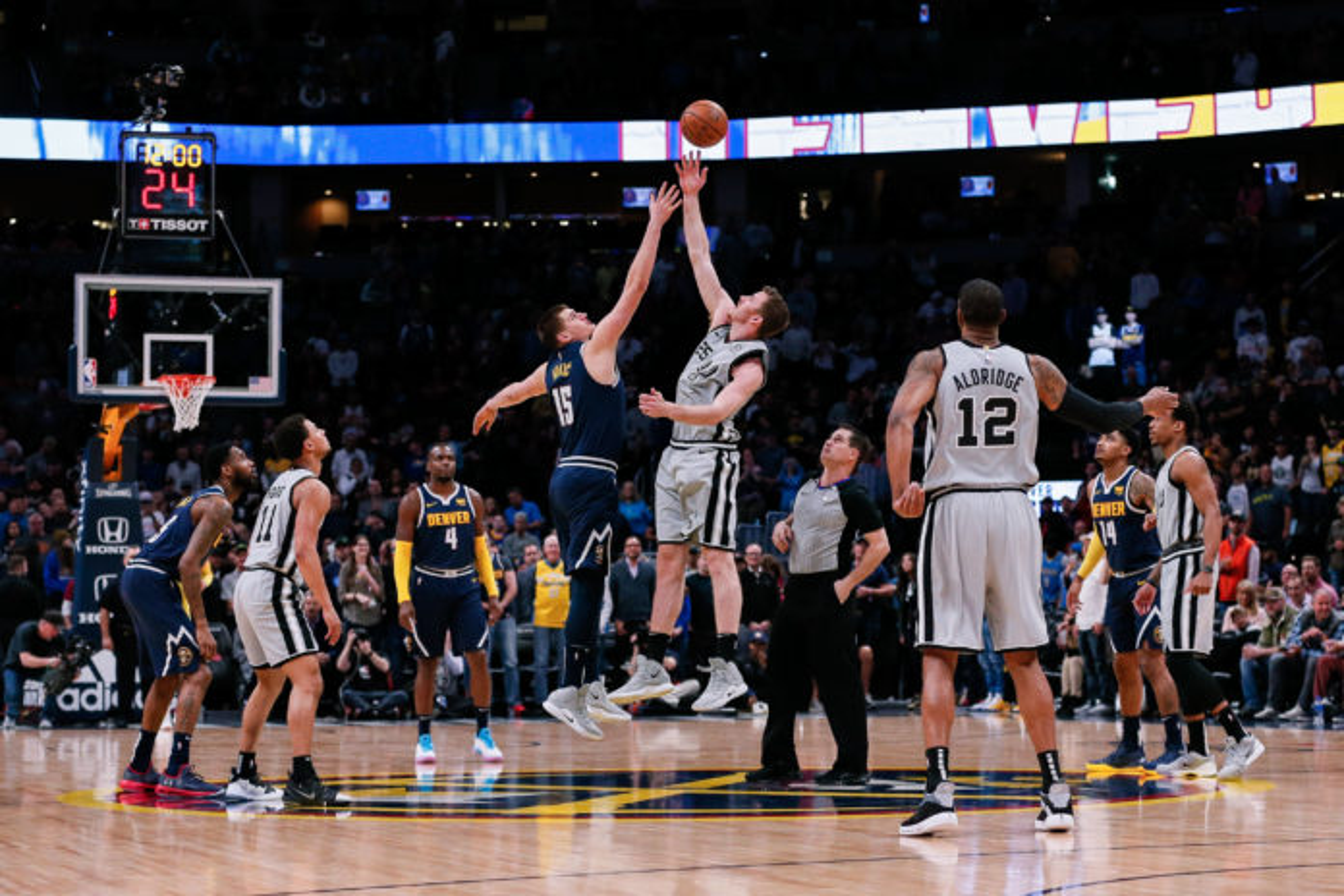 San Antonio Spurs center Jakob Poeltl (25) wins the tip off against Denver Nuggets center Nikola Jokic (15) in the first quarter at the Pepsi Center