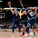 Denver Nuggets center Nikola Jokic (15) tries to pass to guard Jamal Murray (27) as he battles for position against San Antonio Spurs guard Patty Mills (8) in the second quarter at the Pepsi Center.