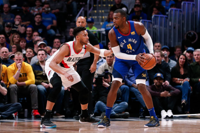 Denver Nuggets forward Paul Millsap (4) controls the ball as Portland Trail Blazers guard Evan Turner (1) defends in the first quarter at the Pepsi Center.