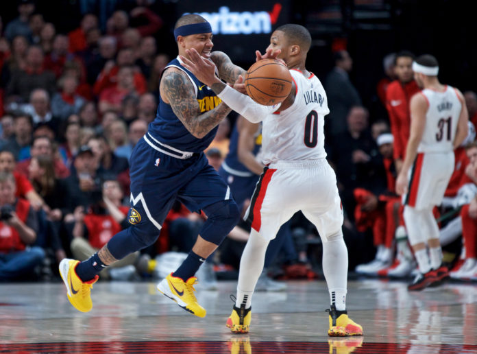 Denver Nuggets guard Isaiah Thomas (0) steals the ball from Portland Trail Blazers guard Damian Lillard (0) during the first quarter at the Moda Center.