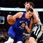 Denver Nuggets center Nikola Jokic (15) drives by San Antonio Spurs center Jakob Poeltl (25) in the second quarter in the first round of the 2019 NBA Playoffs at Pepsi Center.