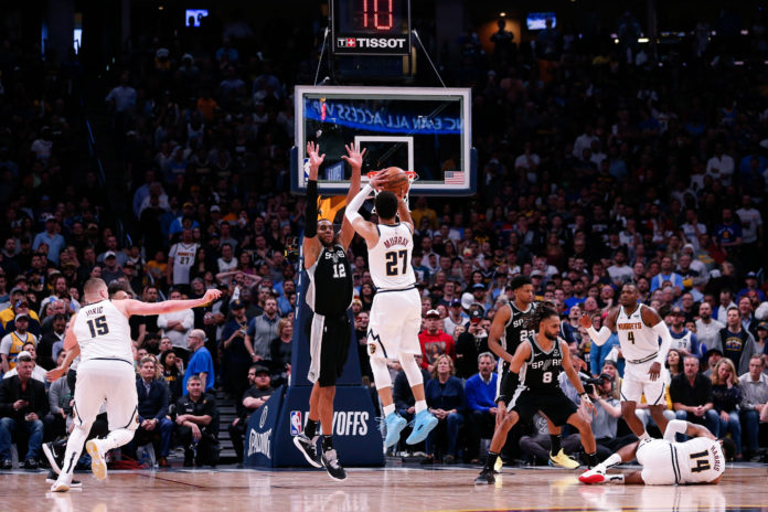 Denver Nuggets guard Jamal Murray (27) attempts a shot against San Antonio Spurs center LaMarcus Aldridge (12) as center Nikola Jokic (15) looks on and guard Patty Mills (8) and forward Rudy Gay (22) defend against guard Gary Harris (14) and forward Paul Millsap (4) in the fourth quarter in game two of the first round of the 2019 NBA Playoffs at the Pepsi Center.