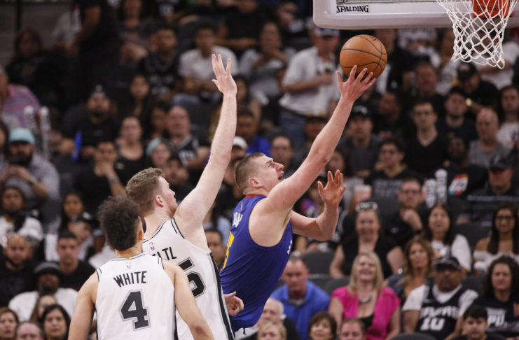 Denver Nuggets center Nikola Jokic (15) shoots the ball past San Antonio Spurs center Jakob Poeltl (left) in game four of the first round of the 2019 NBA Playoffs at AT&T Center.