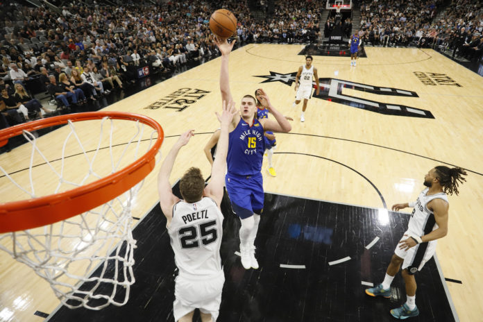 Denver Nuggets center Nikola Jokic (15) shoots the ball over San Antonio Spurs center Jakob Poeltl (25) in game four of the first round of the 2019 NBA Playoffs at AT&T Center.