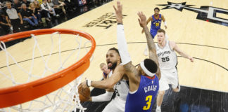San Antonio Spurs point guard Patty Mills (8) shoots the ball under pressure from Denver Nuggets small forward Torrey Craig (3) in game four of the first round of the 2019 NBA Playoffs at AT&T Center.