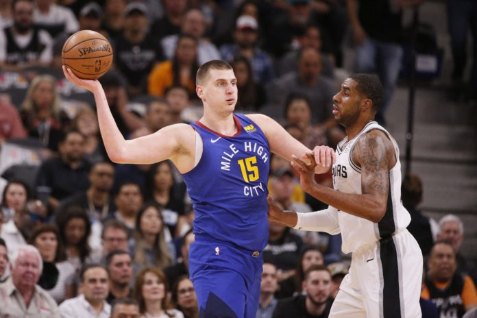 Denver Nuggets center Nikola Jokic (15) looks to pass against San Antonio Spurs power forward LaMarcus Aldridge (right) in game six of the first round of the 2019 NBA Playoffs at AT&T Center