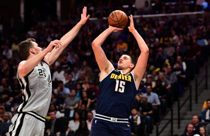Denver Nuggets center Nikola Jokic (15) shoots over San Antonio Spurs center Jakob Poeltl (25) in the first quarter in game seven of the first round of the 2019 NBA Playoffs at the Pepsi Center.