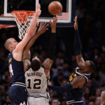 Denver Nuggets forward Mason Plumlee (24) and forward Paul Millsap (4) defend on San Antonio Spurs center LaMarcus Aldridge (12) in the first half in game seven of the first round of the 2019 NBA Playoffs at the Pepsi Center.