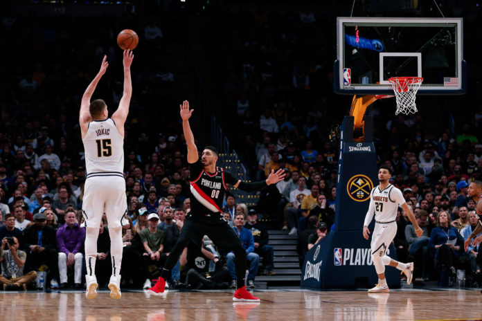Denver Nuggets center Nikola Jokic (15) shoots the ball over Portland Trail Blazers center Enes Kanter (00) in the second quarter in game one of the second round of the 2019 NBA Playoffs at the Pepsi Center.