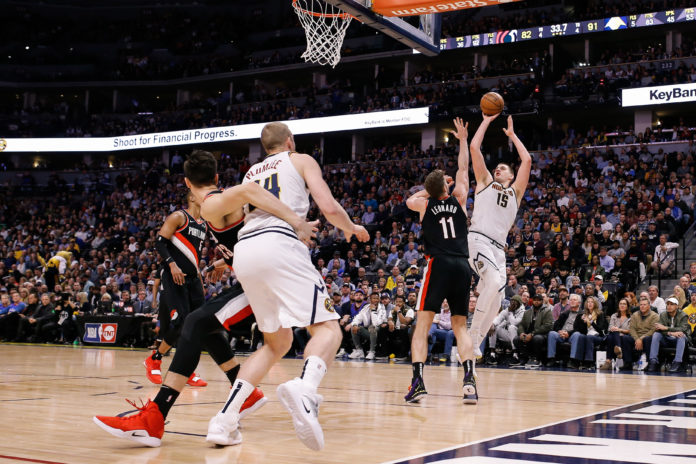 Denver Nuggets center Nikola Jokic (15) shoots the ball over Portland Trail Blazers forward Meyers Leonard (11) as forward Zach Collins (33) and forward Mason Plumlee (24) battle for position in the third quarter in game one of the second round of the 2019 NBA Playoffs at the Pepsi Center.