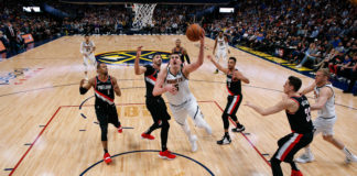 Denver Nuggets center Nikola Jokic (15) shoots the ball past Portland Trail Blazers guard Rodney Hood (5), center Enes Kanter (00), guard CJ McCollum (3) and forward Zach Collins (33) in front of Nuggets forward Mason Plumlee (24) in the third quarter in game one of the second round of the 2019 NBA Playoffs at the Pepsi Center.