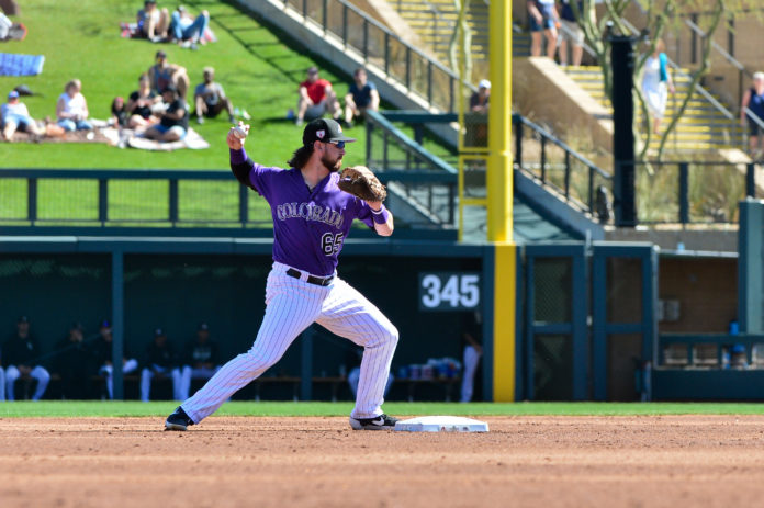 Colorado Rockies shortstop Brendan Rodgers (65) throws to first base during he second inning against the Milwaukee Brewers at Salt River Fields at Talking Stick.