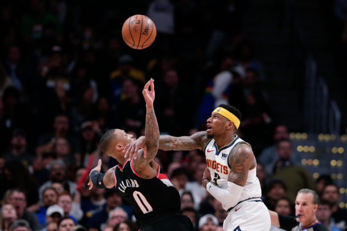 Denver Nuggets forward Torrey Craig (3) fouls Portland Trail Blazers guard Damian Lillard (0) in the third quarter in game one of the second round of the 2019 NBA Playoffs at the Pepsi Center.