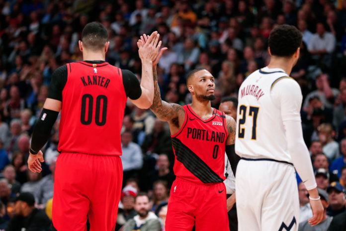 Portland Trail Blazers center Enes Kanter (00) and guard Damian Lillard (0) celebrate in front of Denver Nuggets guard Jamal Murray (27) in the second quarter in game two of the second round of the 2019 NBA Playoffs at the Pepsi Center.