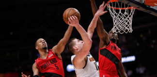 ortland Trail Blazers guard Rodney Hood (5) blocks the shot of Denver Nuggets center Nikola Jokic (15) as forward Al-Farouq Aminu (8) defends in the third quarter in game two of the second round of the 2019 NBA Playoffs at the Pepsi Center.