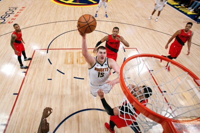 Denver Nuggets center Nikola Jokic (15) drives to the net against Portland Trail Blazers center Enes Kanter (00) and guard Rodney Hood (5) in the fourth quarter in game two of the second round of the 2019 NBA Playoffs at the Pepsi Center.