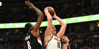Denver Nuggets center Nikola Jokic (15) drives past Portland Trail Blazers forward Al-Farouq Aminu (8) and center Enes Kanter (00) in the third quarter in game five of the second round of the 2019 NBA Playoffs at Pepsi Center.