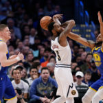 Golden State Warriors guard Andre Iguodala (9) knocks the ball away from Denver Nuggets guard Will Barton (5) as forward Jonas Jerebko (left) looks on in the fourth quarter at the Pepsi Center.