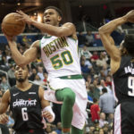 Boston Celtics guard PJ Dozier (50) shoots in between Washington Wizards guard Chasson Randle (9) and forward Troy Brown Jr. (6) during the second quarterat Capital One Arena.