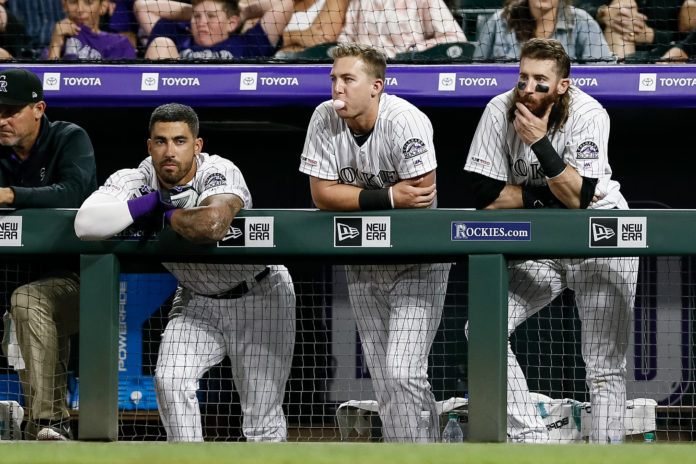 Colorado Rockies center fielder Ian Desmond (20) and second baseman Ryan McMahon (24) and right fielder Charlie Blackmon (19) look on from the dugout in the ninth inning against the San Francisco Giants at Coors Field.
