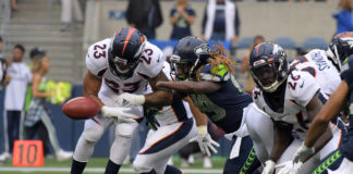 Seattle Seahawks outside linebacker Shaquem Griffin (49) forces a fumble by Denver Broncos running back Devontae Booker (23) in the first quarter at CenturyLink Field.
