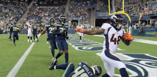 Denver Broncos running back Devontae Jackson (right) scores on a four-yard touchdown pass against Seattle Seahawks linebacker Chris Worley (48) in the fourth quarter at CenturyLink Field. The Seahawks won 22-14.