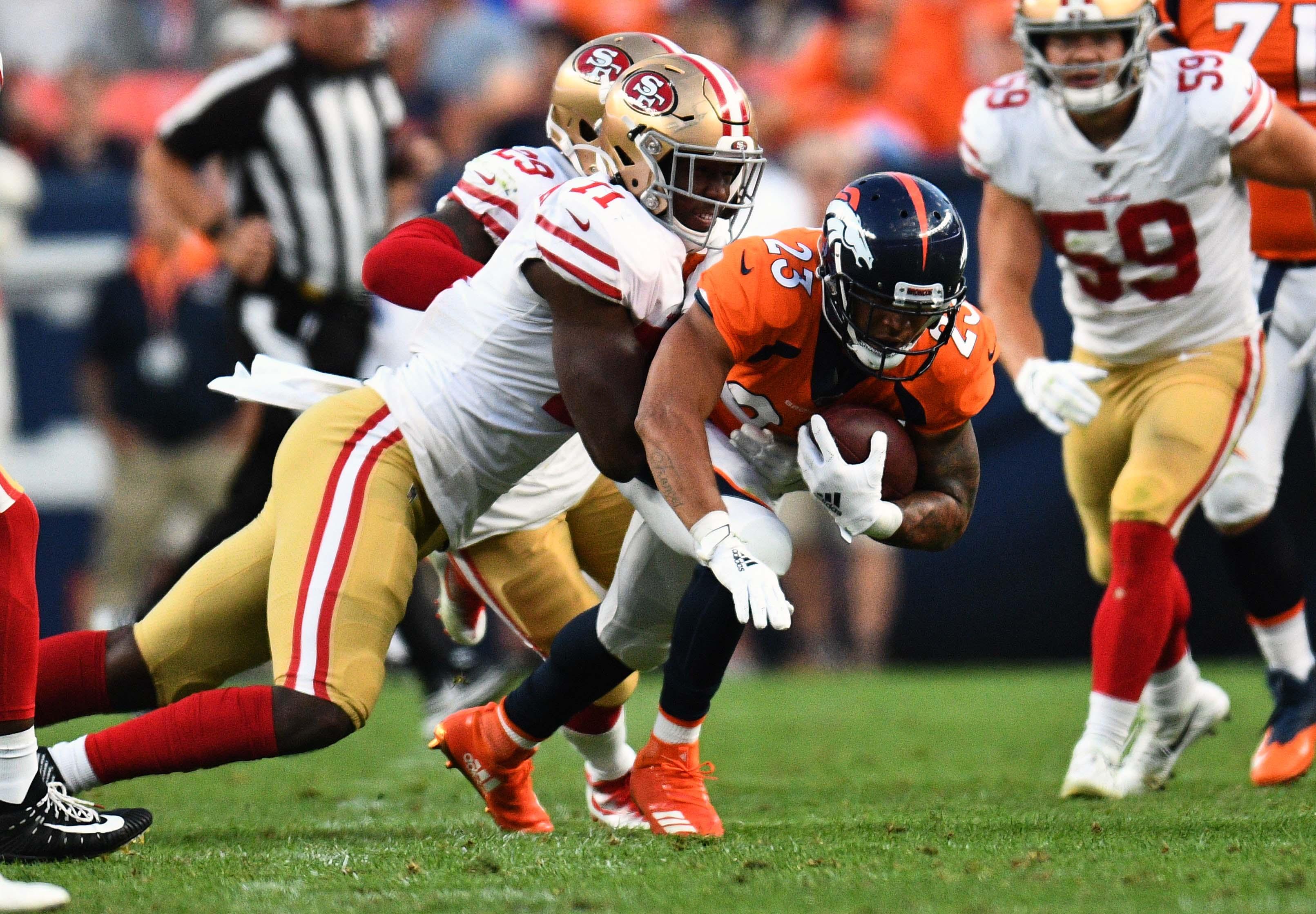 San Francisco 49ers defensive tackle Jullian Taylor (71) tackles Denver Broncos running back Devontae Booker (23) in the second quarter at Broncos Stadium at Mile High.