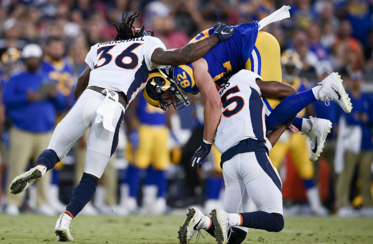 Los Angeles Rams tight end Johnny Mundt (82) is tackled by Denver Broncos safety Dymonte Thomas (35) and Denver Broncos safety Trey Marshall (36) after a catch during the first half at Los Angeles Memorial Coliseum.