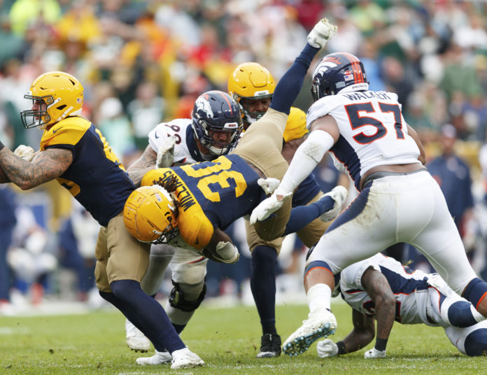 Green Bay Packers running back Jamaal Williams (30) is tackled by Denver Broncos defensive end Adam Gotsis (99) and defensive end DeMarcus Walker (57) during the fourth quarter at Lambeau Field.