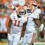 Clemson Tigers linebacker Isaiah Simmons (11) reacts to a defensive play with teammates defensive end Justin Mascoll (7) and defensive tackle Xavier Kelly (back) against the Syracuse Orange during the third quarter at the Carrier Dome.