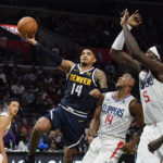 Denver Nuggets guard Gary Harris (14) drives against LA Clippers guard Terance Mann (14) and forward Montrezl Harrell (5) and forward JaMychal Green (right) during the second half at Staples Center.