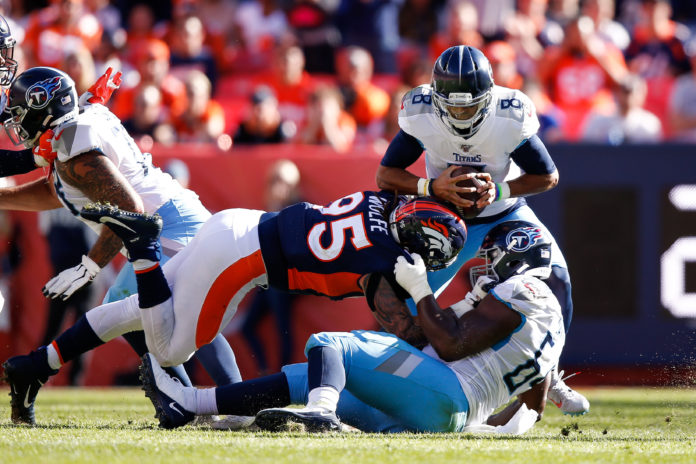 Tennessee Titans quarterback Marcus Mariota (8) is sacked by Denver Broncos defensive end Derek Wolfe (95) as guard Nate Davis (64) defends in the second quarter at Empower Field at Mile High.