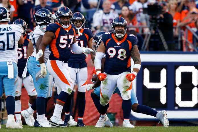 Denver Broncos nose tackle Mike Purcell (98) reacts after a play as defensive end DeMarcus Walker (57) looks on in the fourth quarter against the Tennessee Titans at Empower Field at Mile High.