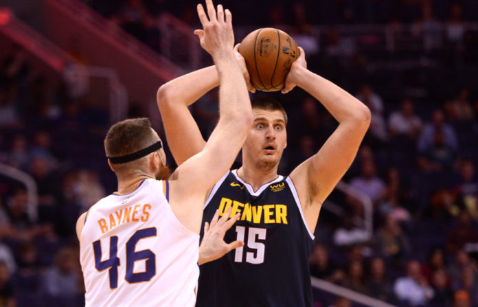 Denver Nuggets center Nikola Jokic (15) controls the ball against Phoenix Suns center Aron Baynes (46) during the second half at Talking Stick Resort Arena.