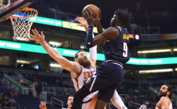 Denver Nuggets forward Jerami Grant (9) is fouled driving to the basket by Phoenix Suns center Aron Baynes (46) during the second half at Talking Stick Resort Arena.