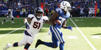 Indianapolis Colts running back Marlon Mack (25) runs away from Denver Broncos linebacker Todd Davis (51) during the first quarter at Lucas Oil Stadium.