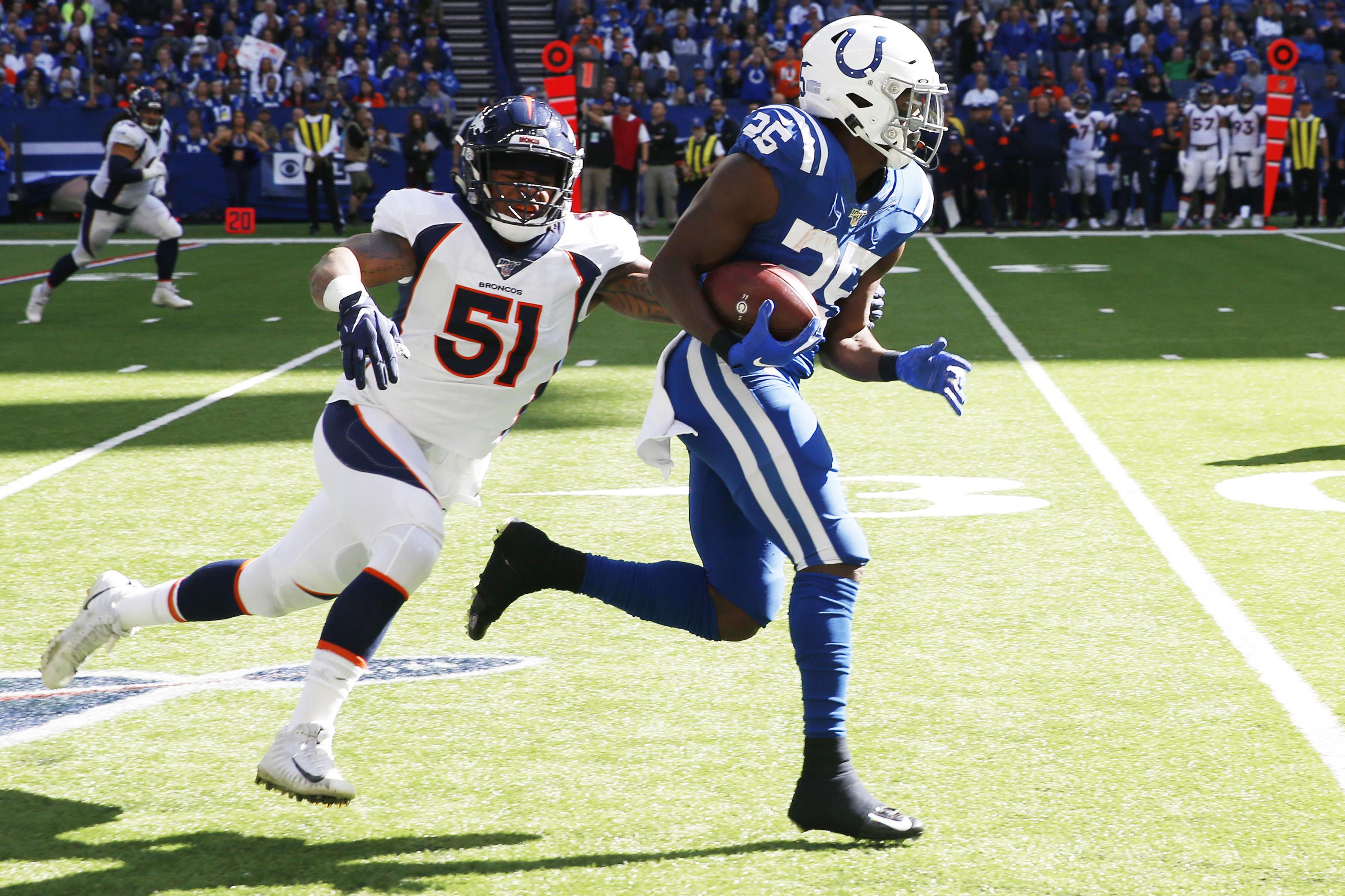 Indianapolis Colts running back Marlon Mack (25) runs away from Denver Broncos linebacker Todd Davis (51) during the first quarter at Lucas Oil Stadium.