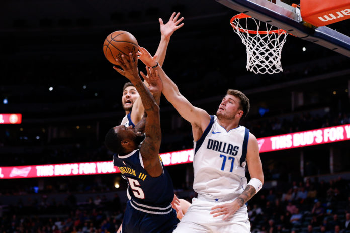 Denver Nuggets guard Will Barton III (5) shoots against Dallas Mavericks forward Maxi Kleber (42) and forward Luka Doncic (77) in the second quarter at the Pepsi Center.