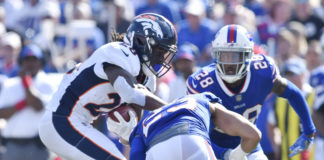 Orchard Park, NY, USA; Denver Broncos running back Jamaal Charles (28) looks to avoid a tackle by Buffalo Bills strong safety Micah Hyde (23) and cornerback E.J. Gaines (28) during the third quarter of a game at New Era Field.
