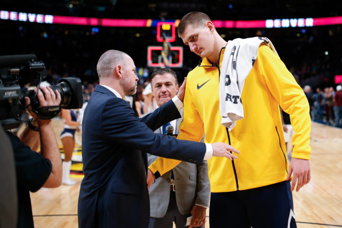 Denver Nuggets head coach Michael Malone congratulates center Nikola Jokic (15) after the game against the Phoenix Suns at the Pepsi Center.