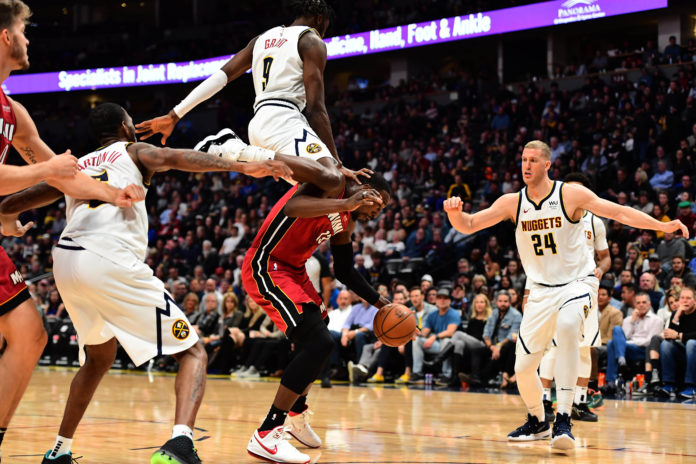 Denver Nuggets forward Jerami Grant (9) lands on the back of Miami Heat forward Bam Adebayo (13) in the third quarter at the Pepsi Center.