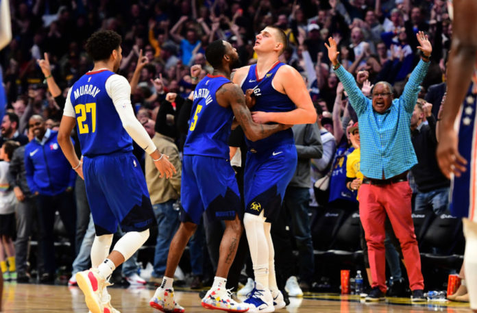 Denver Nuggets center Nikola Jokic (15) is congratulated for his three point basket by forward Will Barton (5) and guard Jamal Murray (27) in the fourth quarter against the Philadelphia 76ers at the Pepsi Center.